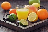 stock photo of sweetie  - Citrus juice and fruits on vintage tray on wooden background - JPG