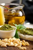 stock photo of pine nut  - Italian basil pesto bruschetta ingredients over old wood macro - JPG