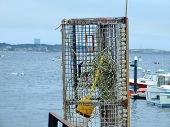 stock photo of lobster trap  - Lobster trap in a vertical position on a boat dock on a cloudy day - JPG