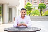 stock photo of colombian currency  - Closeup portrait super happy excited successful young business man holding money dollar bills in hand isolated background of trees building - JPG
