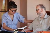 image of grandfather  - companion or grandchild reading to elderly senior or grandfather - JPG
