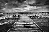 Old wooden jetty, pier, during storm on the sea. Dramatic sky with dark, heavy clouds. Black and white poster