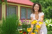 Young Woman Care Of Flowers In Garden Near House