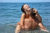 image of nearly nude  - young hot woman sitting astride man in sea near coast closed eyes - JPG