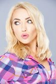 picture of pouting  - Sexy woman with shoulder length blond hair pouting her lips in admiration as she looks back over her shoulder  on grey - JPG