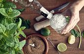 picture of mojito  - hands preparing mojito cocktail with limes and mint - JPG