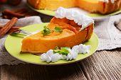 foto of pumpkin pie  - Piece of homemade pumpkin pie on plate on wooden background - JPG