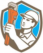 picture of plumber  - Illustration of a plumber holding monkey wrench looking to the side set inside shield crest on isolated background done in retro style - JPG