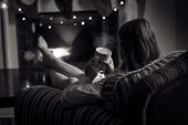 pic of black tea  - Black and white photo of cute woman sitting at fireplace with cup of tea - JPG