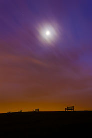 pic of polution  - Light polution produces an orange glow above lonely empty benches on a hilltop near Weymouth - JPG