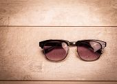 stock photo of protective eyewear  - black sunglasses on wood floor - JPG