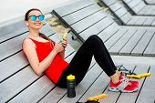 stock photo of jump rope  - Young sporty woman listening to the music on the wooden sunbed with jump rope - JPG