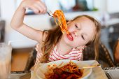 picture of spaghetti  - Portrait of adorable little girl eating spaghetti for a lunch at restaurant - JPG