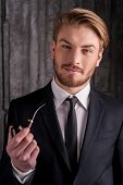 stock photo of toothless smile  - Portrait of handsome young man in formalwear holding a smoking pipe and smiling at camera - JPG