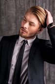 picture of tied hair  - Handsome young man in formalwear touching his hair with hand and looking away - JPG
