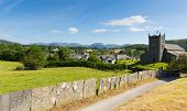 stock photo of english rose  - Beautiful English country village of Hawkshead Lake District Cumbria UK in summer with blue sky church and pink roses - JPG