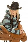 pic of cowgirls  - a cowgirl in her poncho and black hat leaning on her saddle - JPG