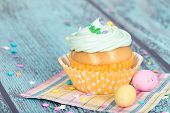 pic of easter candy  - Easter cupcake with candy and sprinkles on green wooden vintage background - JPG