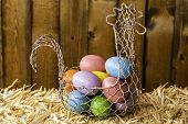 image of chicken-wire  - colored easter eggs in wire basket shaped like chicken on bale of straw with wood background - JPG
