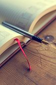 foto of scribes  - Open diary with one fountain pen in it placed on a wood table - JPG