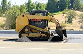 picture of skid-steer  - A paving crew putting down a layer of asphalt on a new highway intersection project - JPG