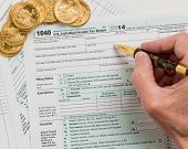 stock photo of irs  - Caucasian hand with pen and solid gold eagle coins on USA tax form 1040 for year 2014 illustrating payment of taxes on forms for the IRS - JPG
