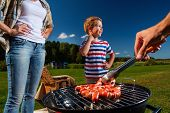 foto of grilled sausage  - Young family preparing sausages on a grill outdoors  - JPG