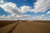stock photo of plowed field  - Large field ready for sowing and plowing action in the spring season - JPG