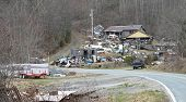 stock photo of neglect  - trash covers the road and hillside in front of a neglected house - JPG
