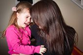 stock photo of misbehaving  - crying little girl being comforted by her mother great parenting image - JPG