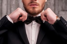 picture of bowing  - Cropped image of handsome young beard man in formalwear adjusting his bow tie - JPG