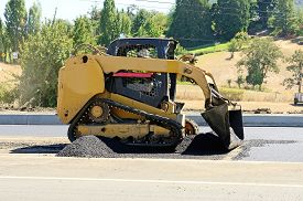 pic of skid-steer  - A paving crew putting down a layer of asphalt on a new highway intersection project - JPG