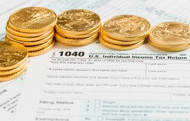stock photo of irs  - Solid gold eagle coins on USA tax form 1040 for year 2014 illustrating payment of taxes on forms for the IRS