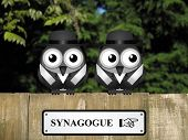 foto of synagogue  - Two Jewish birds with Synagogue sign perched on a timber garden fence against a foliage background - JPG