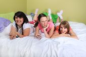 stock photo of slumber party  - Group of three teenage girls hanging out on a bed in their pajamas ready for a sleepover or slumber party - JPG
