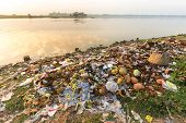 foto of polluted  - Rubbish pollution with plastic and other packaging stuffs on the bank of the Taungthaman lake near U Bein bridge in Myanmar  - JPG