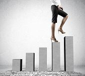 foto of step-up  - Young businesswoman stepping up on chart bar - JPG