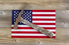 image of labor  - Old hammer and a United States of America flag on rustic wood - JPG