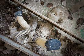 image of beheaded  - Old doll placed under two metal beams in an abandoned kindergarten in Pripyat  - JPG