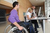 stock photo of people work  - Man in wheelchair working in the office - JPG