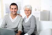 Elderly woman with young man using internet at home