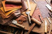 Leather craft or leather working. Selected pieces of beautifully colored or tanned leather on leathe poster