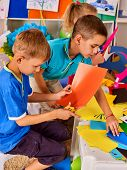 Child cutting paper in class. Kids development and social lerning children in school. Childrens pro poster