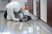 Pest control man spraying pesticide under the cabinet in kitchen poster