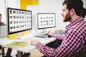 Side view of young male editor working on photos at creative office poster