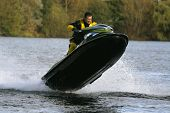 A jet ski rider and his personal watercraft leaping out of the water