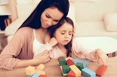 Mom Teaches Daughter. Educational Games. Learning Child At Home. Build House Of Cubes. Woman And Sad poster