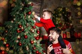 Happy Father And Son Enjoying Decorating Christmas Tree With Christmas Balls And Light Garland Prepa poster