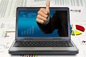 Business hand thumps up come out of the laptop screen on financial Graphs