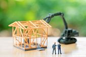 Miniature Businessmen Standing Investment Analysis Housing Or Investment In Movable Property. Using poster